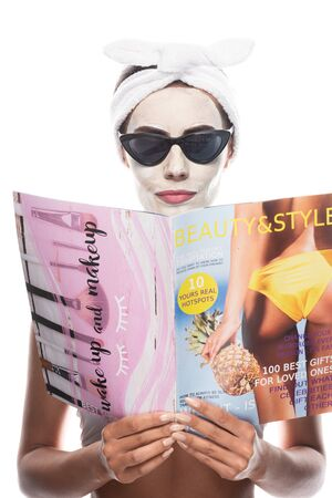 front view of woman in cosmetic hair band and sunglasses with facial mask reading magazine isolated on white