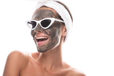 nude young woman in cosmetic hair band and sunglasses with clay mask on face laughing isolated on white 스톡 콘텐츠