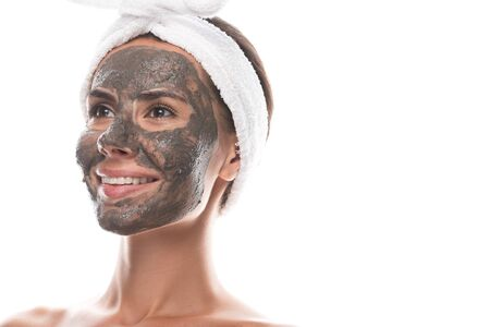 nude young woman in cosmetic hair band with clay mask on face smiling and looking away isolated on white Stockfoto