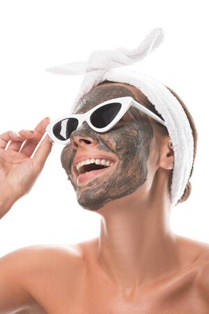 nude smiling young woman in cosmetic hair band and sunglasses with clay mask on face isolated on white Stockfoto