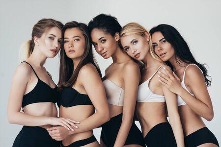 cinq jeunes femmes multiethniques en sous-vêtements embrassant isolés sur fond gris