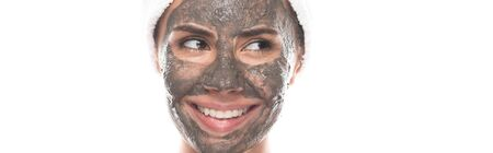 panoramic shot of smiling woman with clay mask on face looking away isolated on white Stockfoto