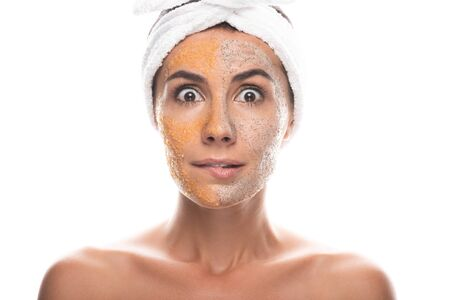 front view of shocked young woman in cosmetic hair band with scrub on face isolated on white