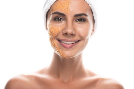 front view of smiling young woman in cosmetic hair band with scrub on face isolated on white