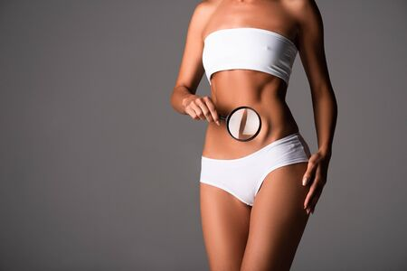 cropped view of sexy young woman in underwear holding magnifying glass isolated on grey