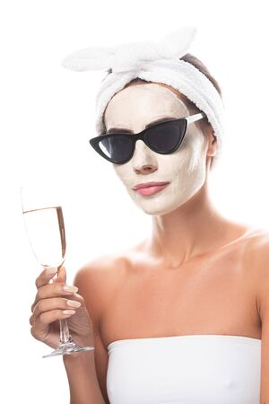 woman in sunglasses and cosmetic hair band with facial mask holding wine glass isolated on white