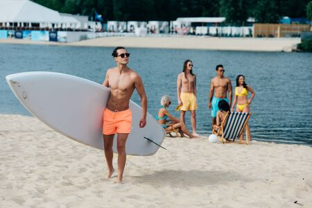handsome man holding surfboard while multicultural friends resting on riverside