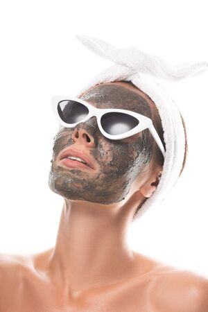 nude young woman in cosmetic hair band and sunglasses with clay mask on face isolated on white Stockfoto