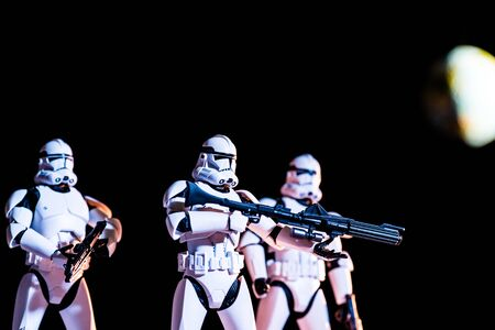 KYIV, UKRAINE - MAY 25, 2019: white imperial stormtroopers with guns on black background with blurred planet Earth