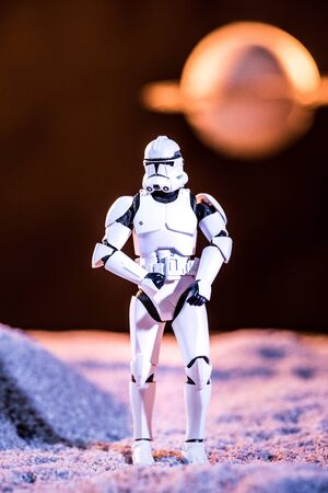 KYIV, UKRAINE - MAY 25, 2019: white imperial stormtrooper on cosmic planet on dark background
