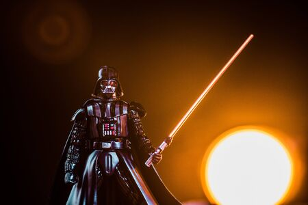 KYIV, UKRAINE - MAY 25, 2019: Darth Vader figurine with lightsaber on black background with shining sun Sajtókép
