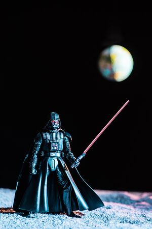 KYIV, UKRAINE - MAY 25, 2019: Darth Vader figurine with lightsaber on black background with planet Earth