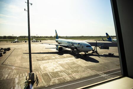 ROME, ITALY - JUNE 28, 2019: airplanes at aerodrome under sky in sunny day behind window