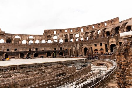 ROME, ITALY - JUNE 28, 2019: ruins of colosseum and tourists under grey sky Editorial