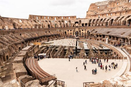 ROME, ITALY - JUNE 28, 2019: crowd of tourists in colosseum under grey sky