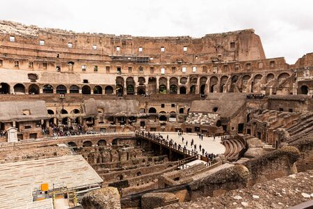 ROME, ITALY - JUNE 28, 2019: ruins of colosseum and crowd of tourists under grey sky Editorial