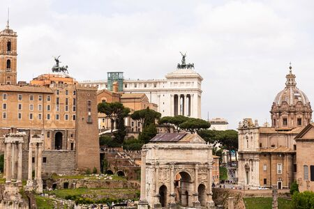 ROME, ITALY - JUNE 28, 2019: tourists walking at roman forum with ancients buildings