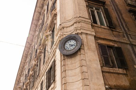 ROME, ITALY - JUNE 28, 2019: bottom view of old building with clock in rome, italy