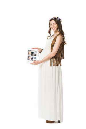 KYIV, UKRAINE - FEBRUARY 4, 2019: full length view of smiling pregnant boho woman holding digital tablet with pinterest app on screen isolated on white Editorial