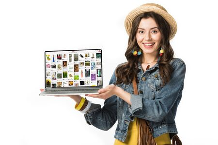 KYIV, UKRAINE - FEBRUARY 4, 2019: smiling hippie girl in straw hat holding laptop with pinterest website on screen isolated on white