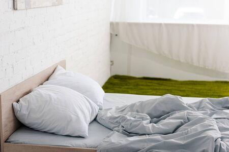 Houten bed met kussens en verfrommelde lichte deken in witte kamer met groen tapijt