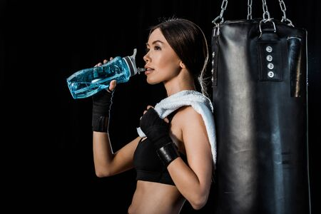 attractive girl drinking water from sport bottle and standing near punching bag isolated on black Reklamní fotografie