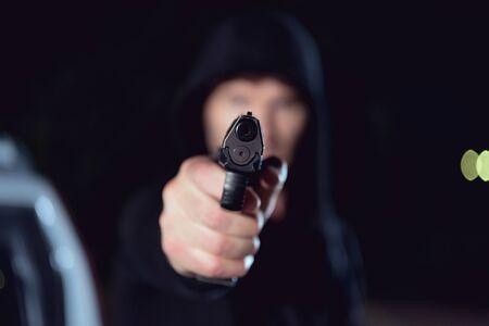 selective focus of gun in hand of thief in black hoodie Imagens