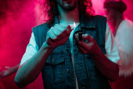 cropped view of man lighting smoking pipe with marijuana in nightclub