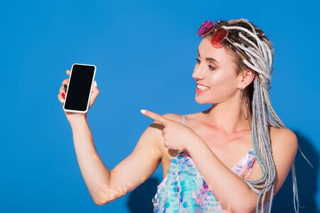 beautiful stylish girl pointing with finger at smartphone with blank screen on blue Фото со стока