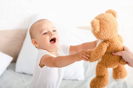 흰 옷을 입은 귀여운 어린 아이가 입을 벌리고 웃고 손을 들고 갈색 봉제 곰