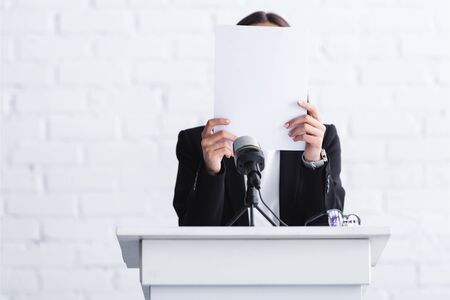 scared lecturer suffering from logophobia and hiding face behind paper while standing at podium tribune