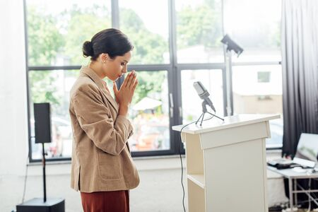 side view of attractive businesswoman praying during conference in conference hall Reklamní fotografie