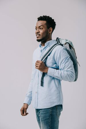 curly african american man standing with backpack isolated on grey Stock Photo