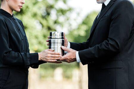 przycięty widok starszego mężczyzny i kobiety trzymającej urnę pogrzebową