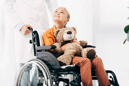 cropped view of pediatrist in white coat and kid with teddy bear on wheelchair