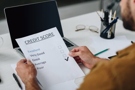 selective focus of young adult man holding credit score