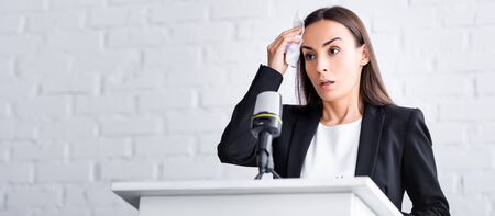panoramic shot of worried lecturer suffering from fear of public speaking holding napkin near forehead while standing on podium tribune