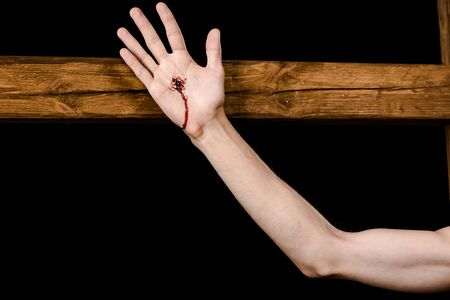cropped view of jesus crucified on wooden cross isolated on black