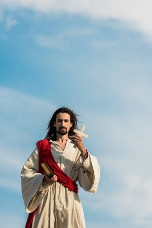 jesus holding holy bible and cross against blue sky outside