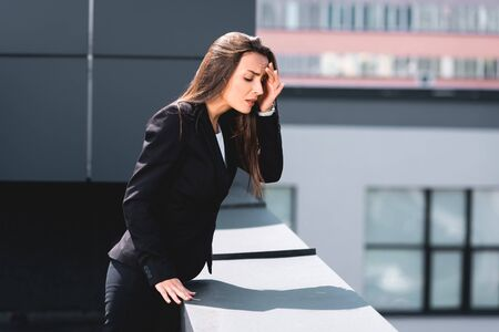 anxious businesswoman, suffering from acrophobia, standing on rooftop and looking down
