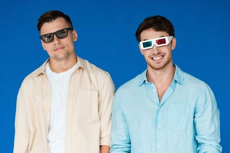 front view of two smiling friends in 3d glasses isolated on blue Stock fotó