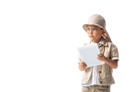 pensive explorer child in glasses and hat holding digital tablet and looking away isolated on white Banco de Imagens - 130111350