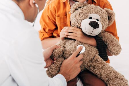 partial view of kid and pediatrist in white coat examining teddy bear with stethoscope Imagens