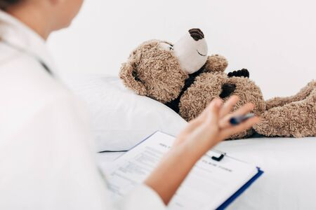 partial view of child in doctor costume examining teddy bear