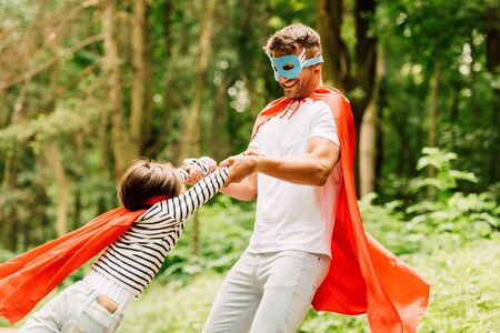 father in cloak and mask spinning little boy in red superhero cloak Stock Photo
