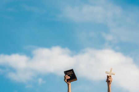 cropped view of man holding holy bible and cross against blue sky with clouds