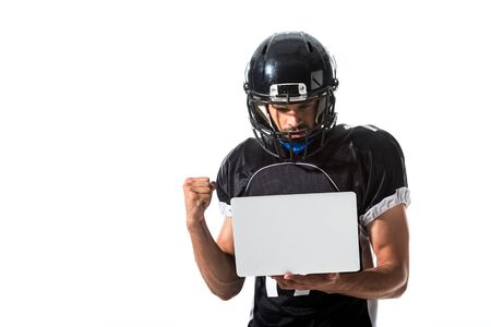 American Football player with laptop cheering with clenched hand Isolated On White