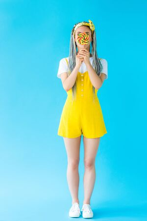 girl with dreadlocks covering face with lollipop on turquoise 版權商用圖片