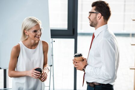 handsome bearded businessman holding disposable cup and looking at cheerful blonde woman in office Foto de archivo