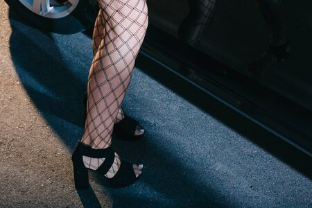Ausgeschnittene Ansicht einer Frau in Netzstrümpfen, die in Schuhen in der Nähe des Autos steht Standard-Bild